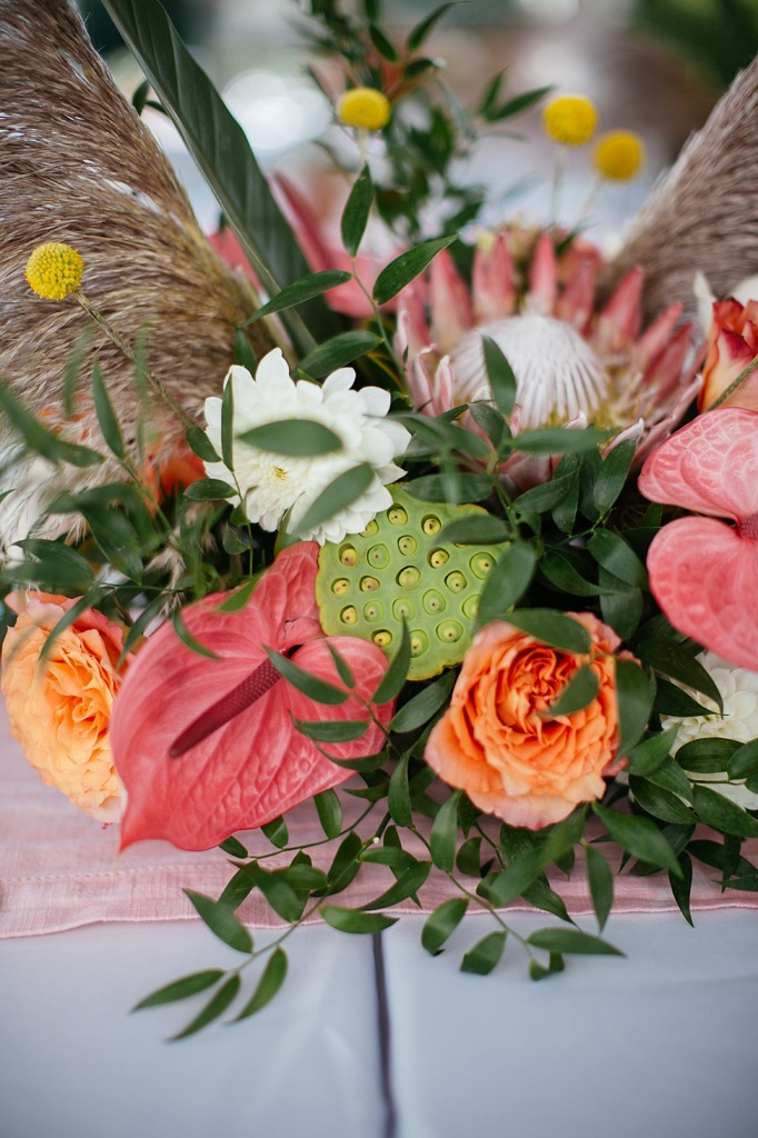 The wedding florals were done with pink, orange and white blooms, king proteas and greenery