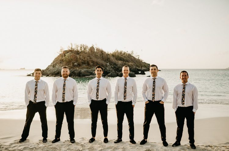 The groom and groomsmen were wearing black pants, white shirts and dark floral ties