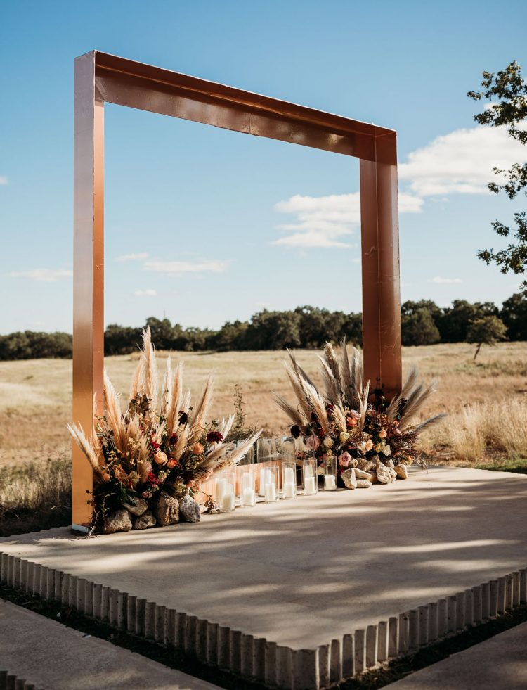 The wedding arch was a copper one, with lush florals, pampas grass and pillar candles