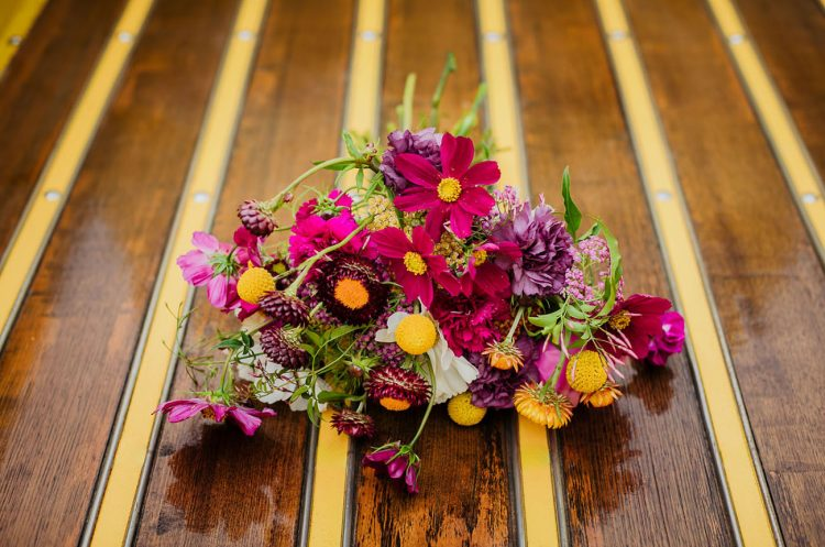 The wedding bouquet was done with fuchsia, purple and hot pink blooms and billy balls