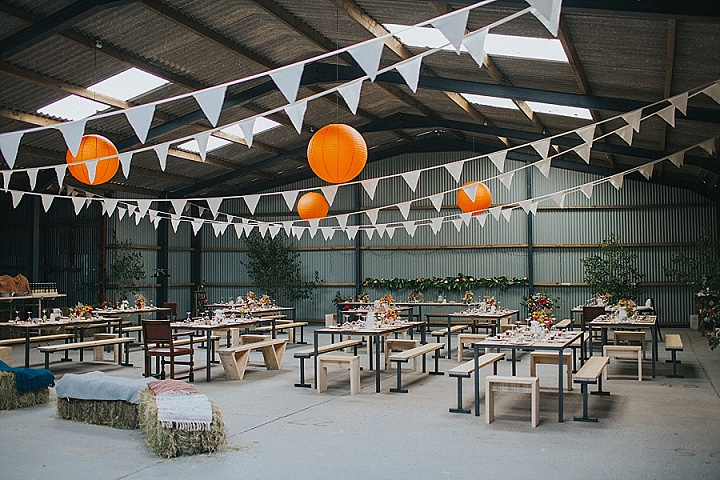 The venue was a barn completely decorated by the couple and the bride's family, there was hay, paper buntings and lanterns and bright blooms