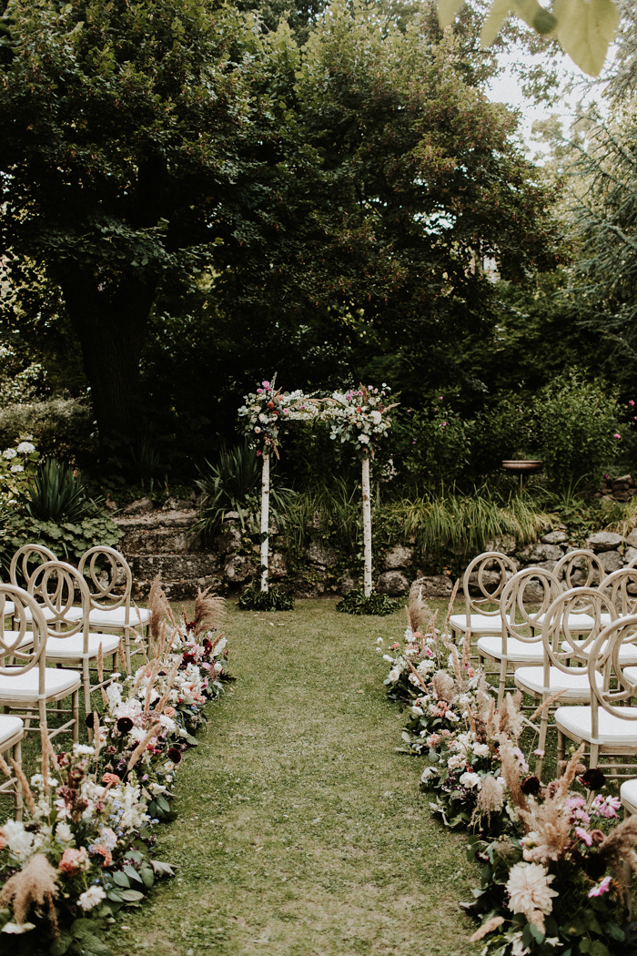 The wedding arch was decorated with lush blooms and greenery and the wedding aisle was decorated with them, too