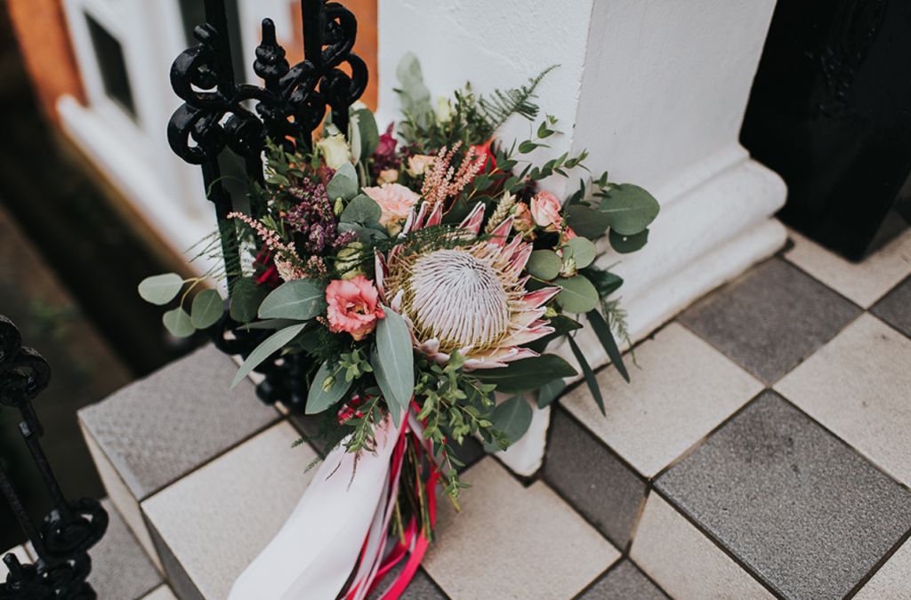 The wedding bouquet was done with pink blooms, a king protea and greenery and colorful ribbons