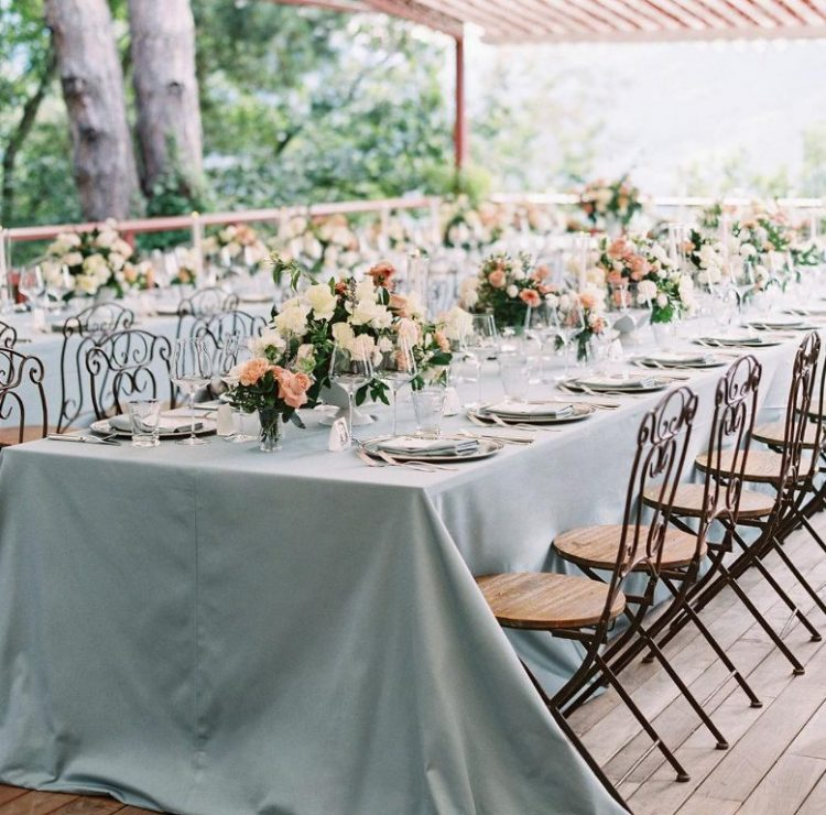 The wedding tablescapes were done with powder blue tablecloths, neutral and pink blooms and blue napkins