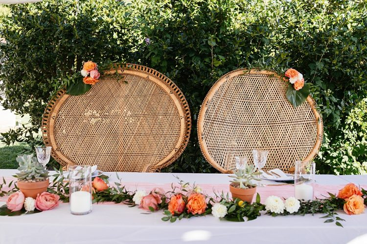 The wedding decor was done with orange, pink and white blooms, greenery and candles