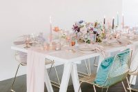 08 The wedding tablescape was done with blush linens, pastel blooms, colorful candles and glasses