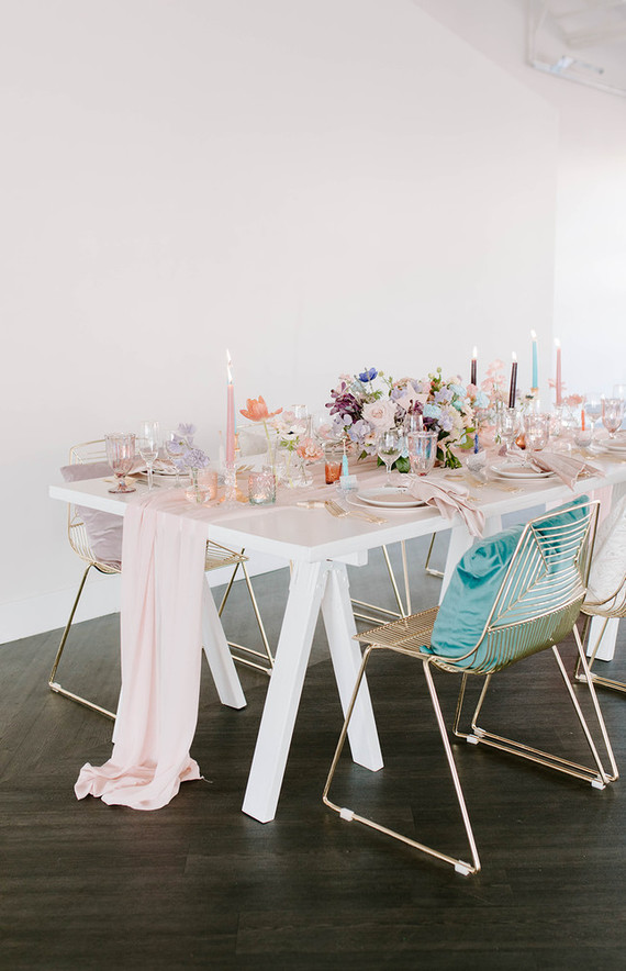 The wedding tablescape was done with blush linens, pastel blooms, colorful candles and glasses