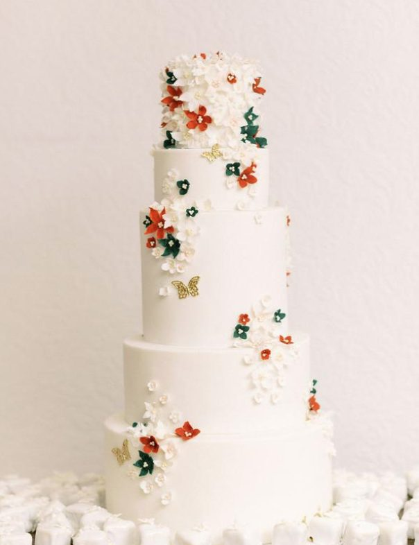 The couple served a white wedding cake with white, red and green blooms and gold butterflies
