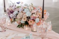 09 The sweetheart table was done with pastel pink and blue linens, pastel blooms, black candles