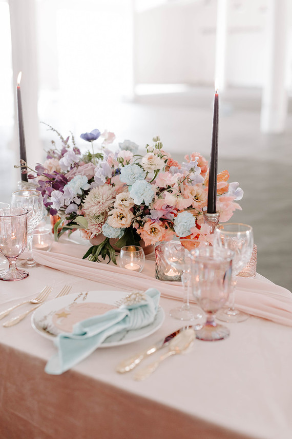 The sweetheart table was done with pastel pink and blue linens, pastel blooms, black candles