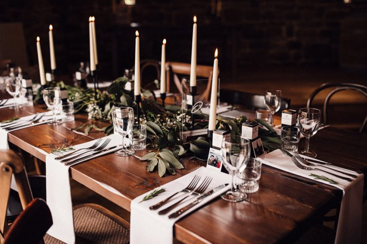 The wedding tablescapes were done with greenery, white blooms, candles and white linens