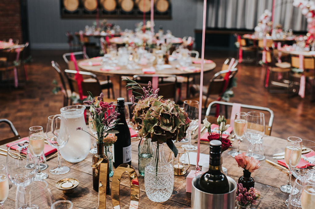 The wedding tablescapes were done with pink blooms and greenery, gold candle holders and table numbers