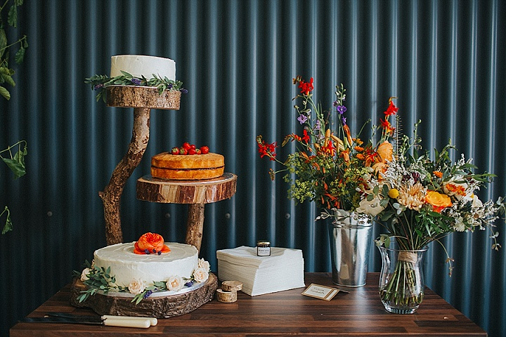 There were several homemade wedding cakes served on a natural wood slice stand and decorated with blooms