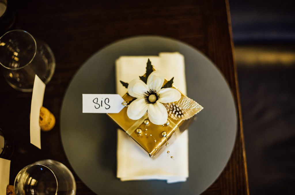 Each place setting was marked with a gold favor box with faux blooms and feathers