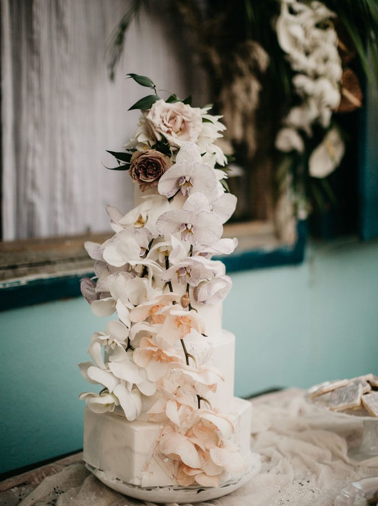 The wedding cake was a white marble one, with blush and peachy orchids and roses on top