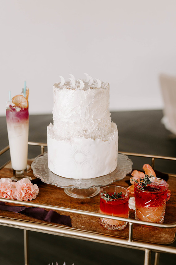 The wedding cake was white, with much texture, moons on top and a sun
