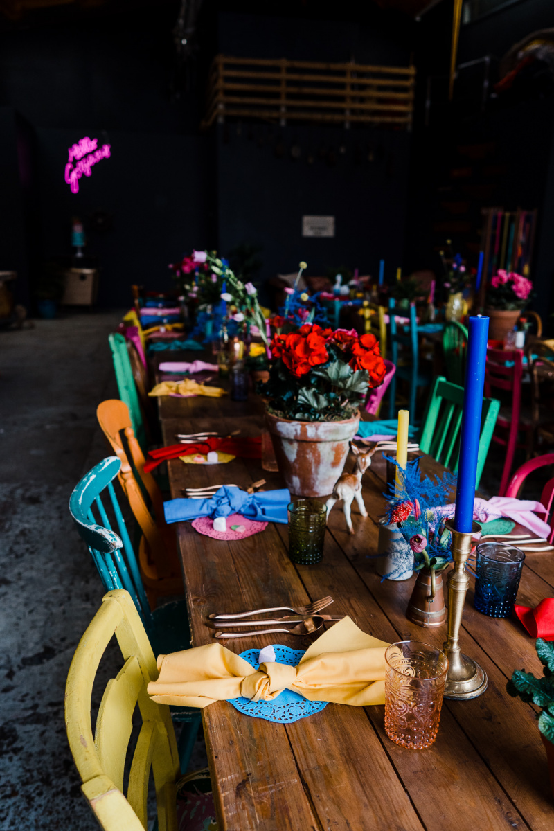 The wedding tablescapes were done with colorful napkins, doilies, blooms, candles and mismatching chairs