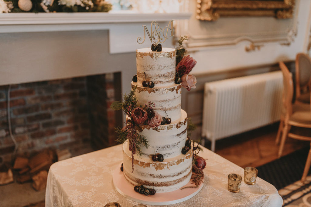 The wedding cake was a naked one, with burgundy and blush blooms, greenery and gilded berries