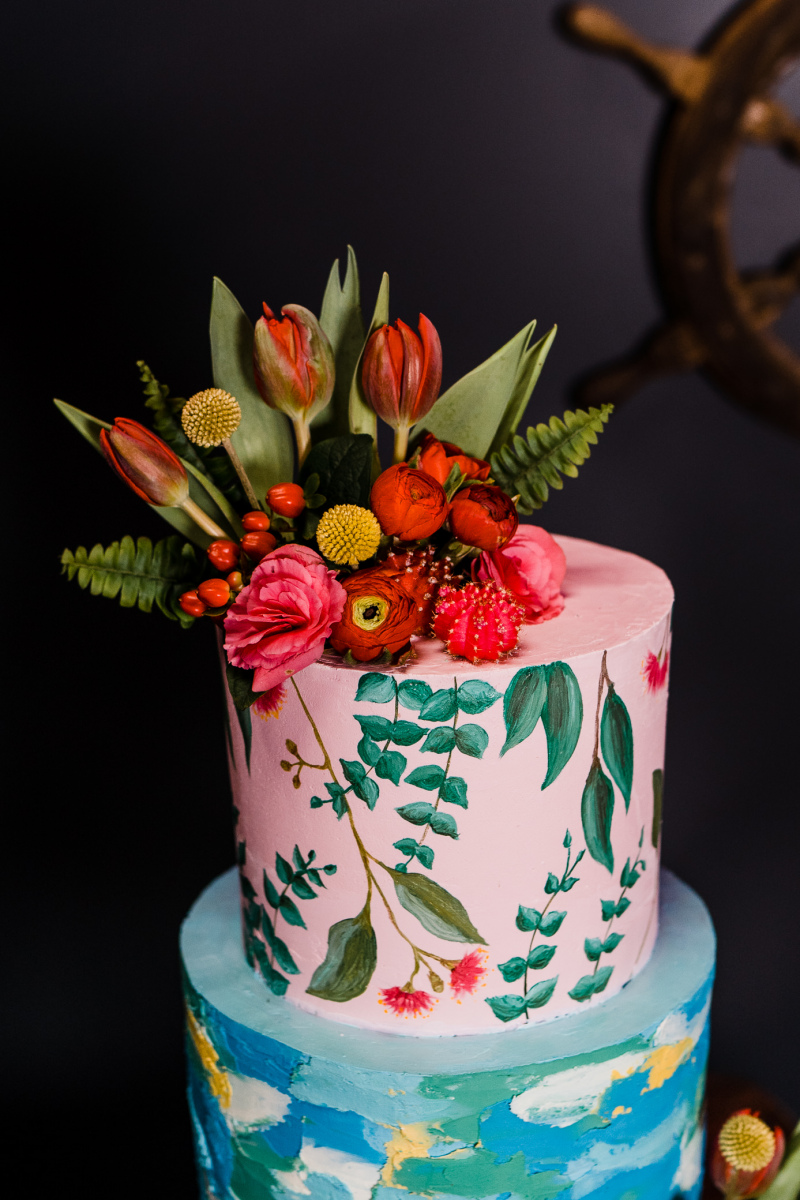 The wedding cake featured a bright abstract tier and a botanical painted one, bright blooms and leaves and cacti