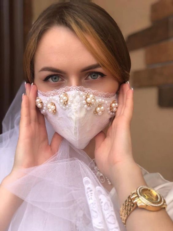 a white lace embellished face mask with pearls is a stylish glam option to go for, it will perfectly accent a bridal look