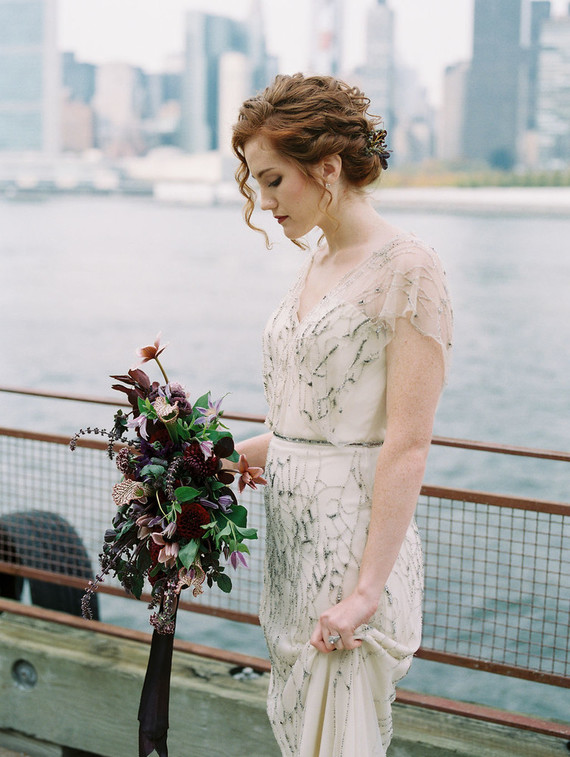 One bride was wearing a romantic embellished art deco wedding dress with a V-neckline, statement earrings and a chic wavy updo
