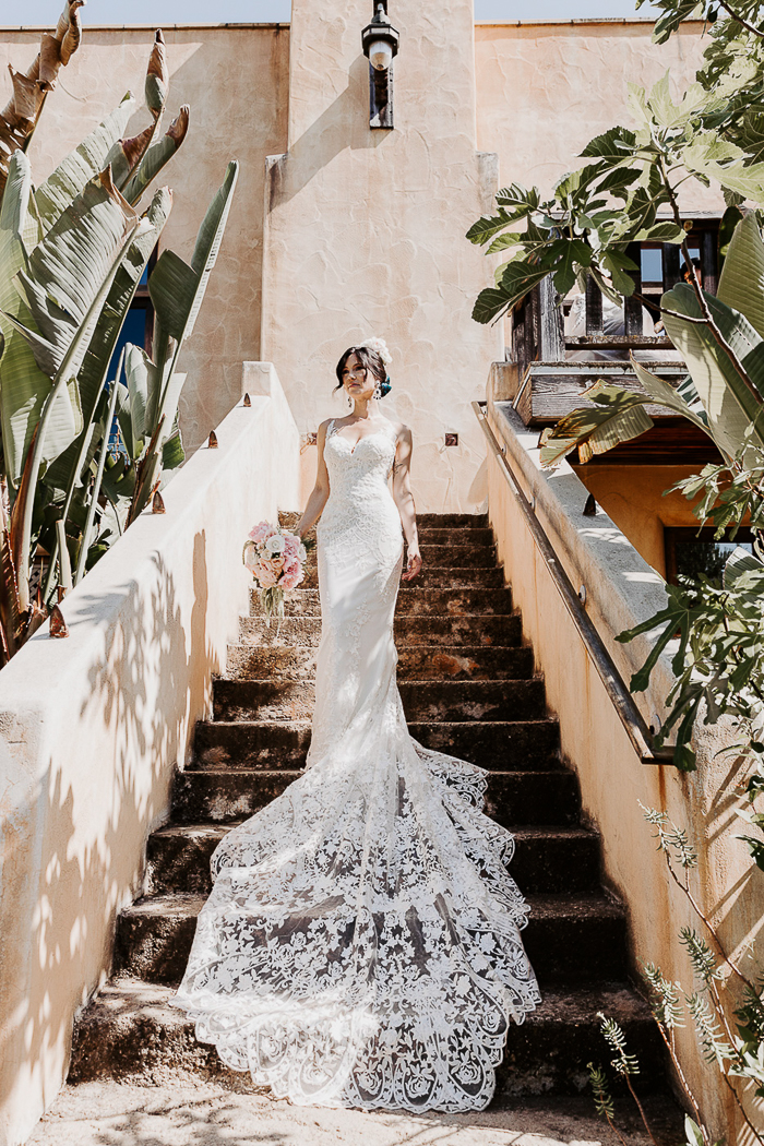 The bride was wearing a breathtaking lace mermaid wedding dress with no sleeves but a peacock-like train