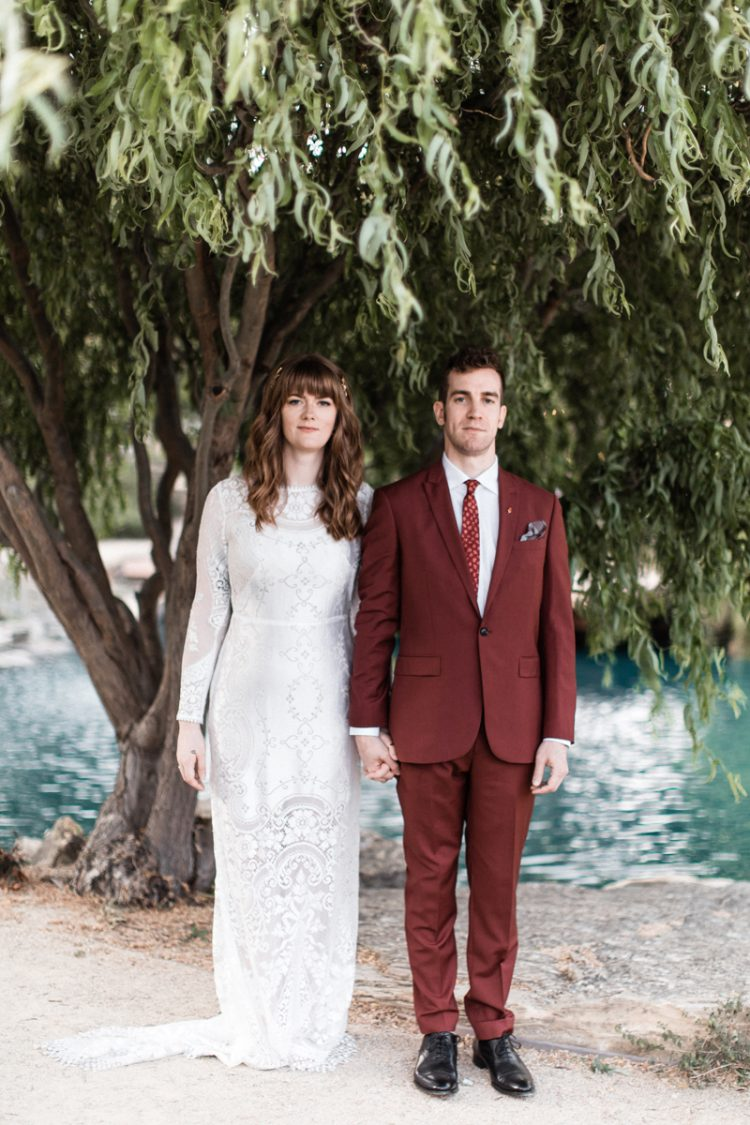 The bride was wearing a chic lace sheath wedding dress with long sleeves, a high neckline and a train and the groom was wearing a burgundy suit with a red printed tie