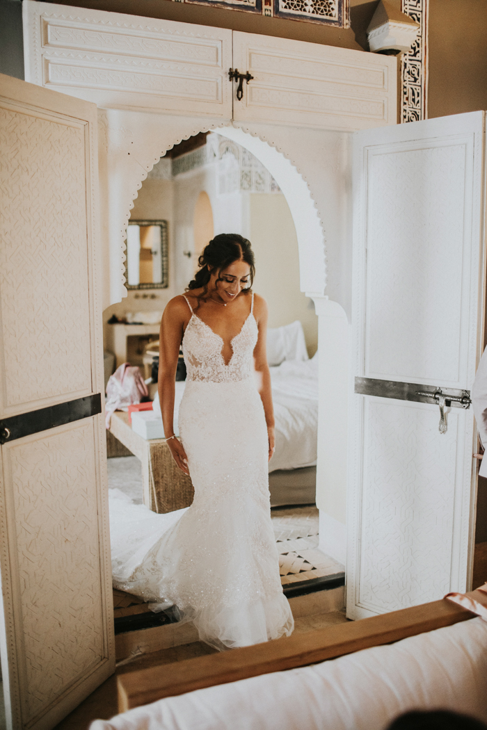 The bride was wearing a fantastic lace embellished sheath wedding dress with a plunging neckline and a train