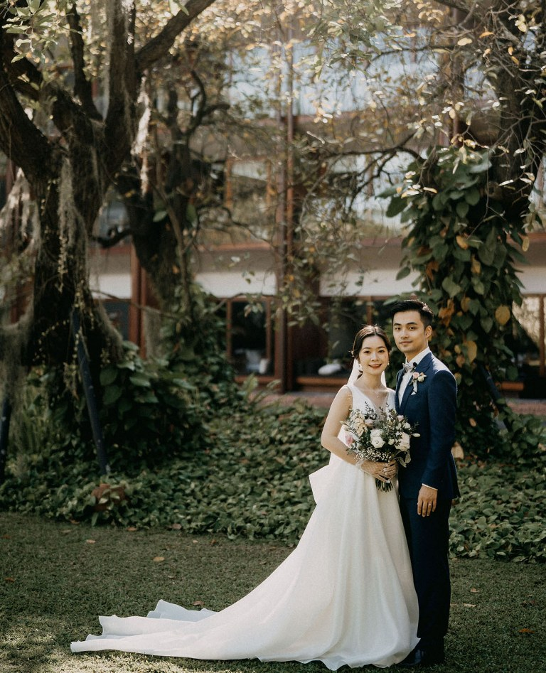 The bride was wearing a gorgeous modern wedding ballgown with a deep neckline, a long train and a veil, the groom was rocking a navy suit and a printed bow tie
