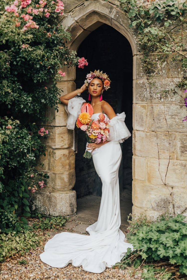 The first wedding dress was a plain strapless sheath one, with a train and tulle sleeves plus a bold floral crown and a bright wedding bouquet