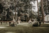 02 The wedding ceremony space was done with wooden benches and an arch, with blush blooms, greenery and pampas grass