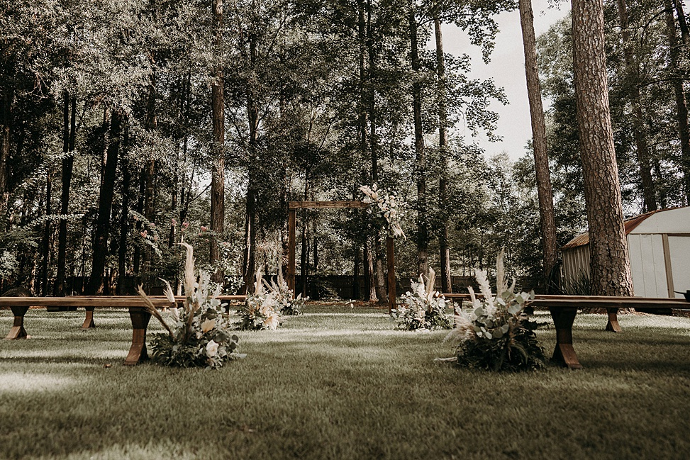 The wedding ceremony space was done with wooden benches and an arch, with blush blooms, greenery and pampas grass