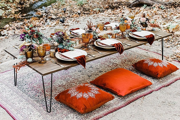 The wedding tablescape was done with bright blooms, greenery, amber glasses and orange napkins