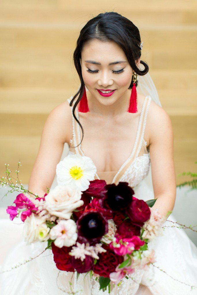 The bride rocked a fuchsia lipstick and red tassel earrings and carried a bold purple, fuchsia and blush wedding bouquet