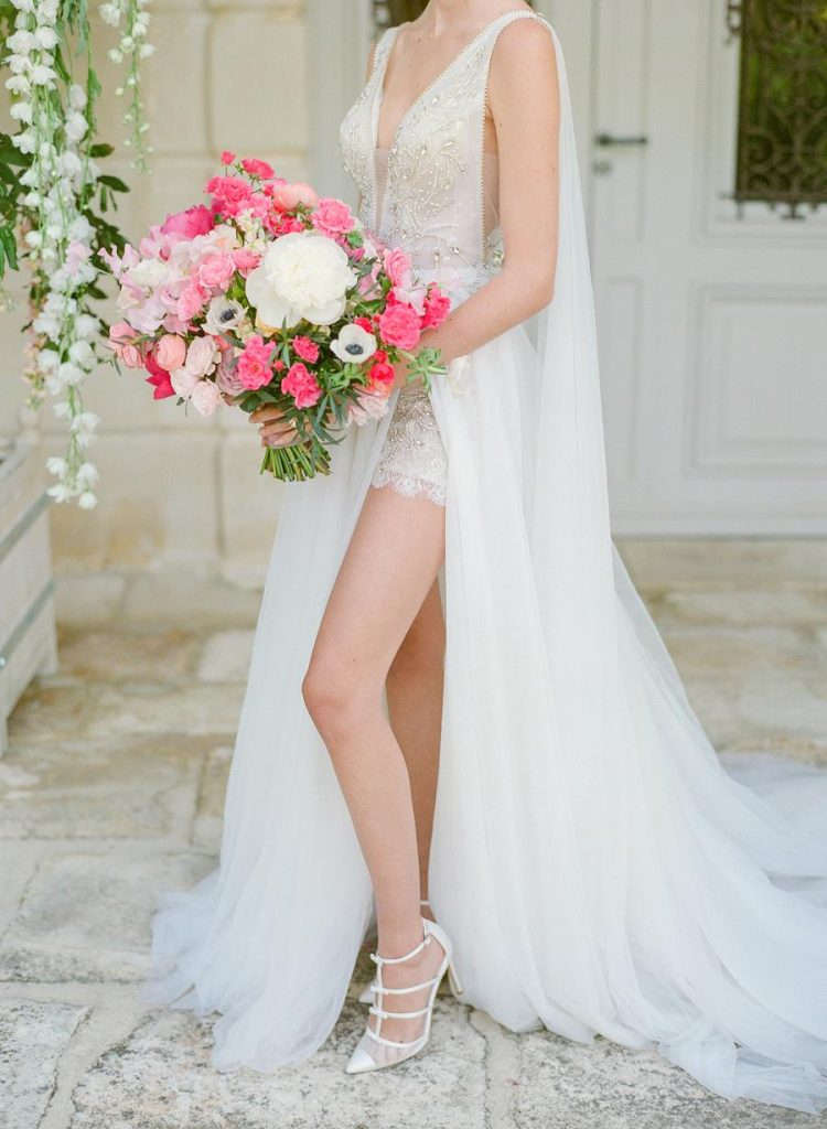 The bride was wearing a gorgeous embellished wedding dress with a plunging neckline, a cape and an overskirt