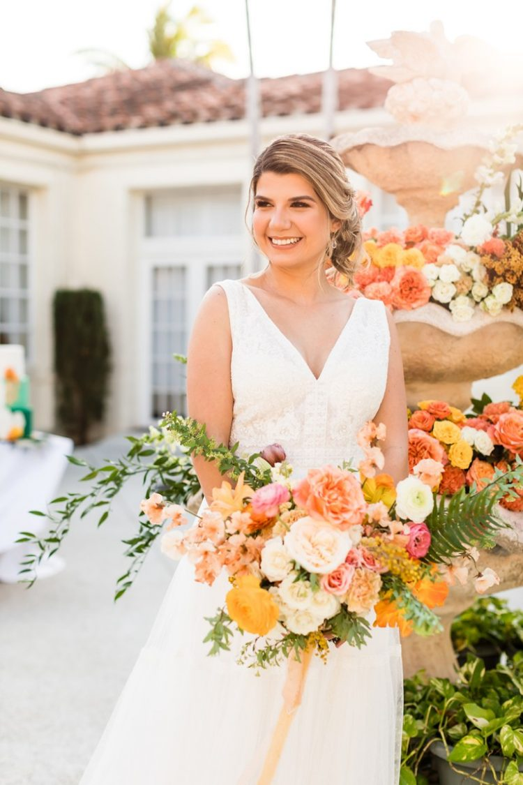 The bride was wearing a lace sleeveless A-line wedding dress with a deep V-neckline and carrying a bright textural bouquet