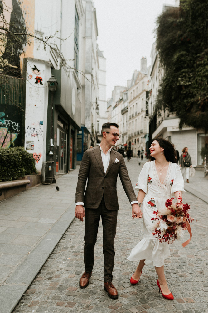 The bride was wearing a white midi dress with red floral embroidery, red shoes and a red lip