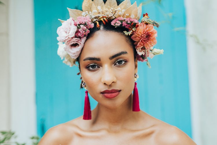 The floral and dried leaf crown was paired with hot pink tassel earrings and a pink lip