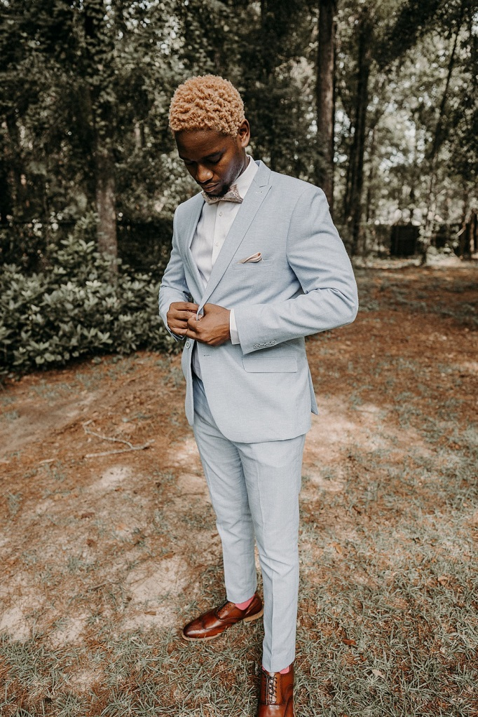The groom was wearing a powder blue suit, a printed bow tie and brown shoes