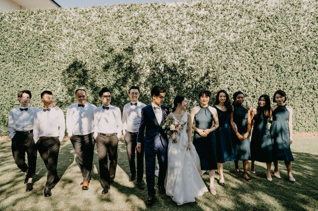 The groomsmen were wearing black pants and bow ties and white shirts, and bridesmaids were wearing navy halter neckline midi dresses