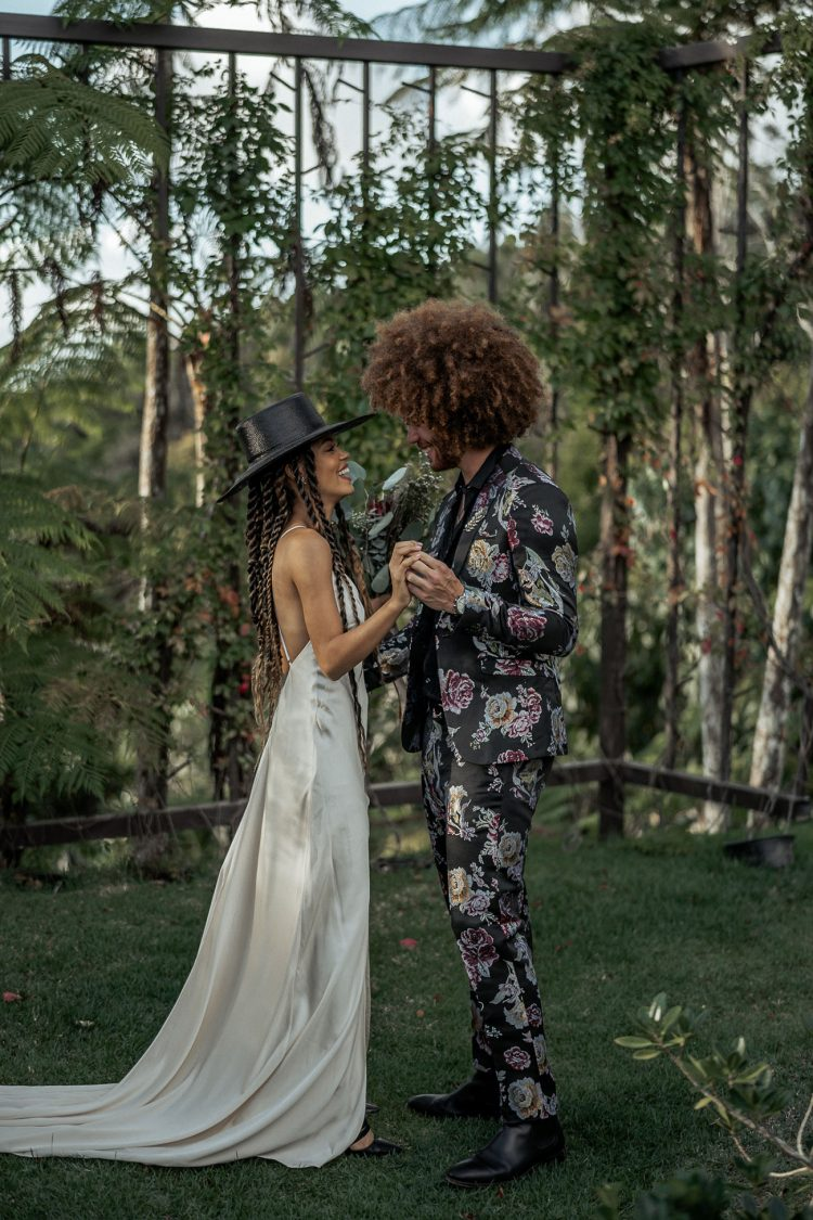 The groom was wearing a black floral suit, a black shirt and boots and his Afro hair perfectly finished off his look