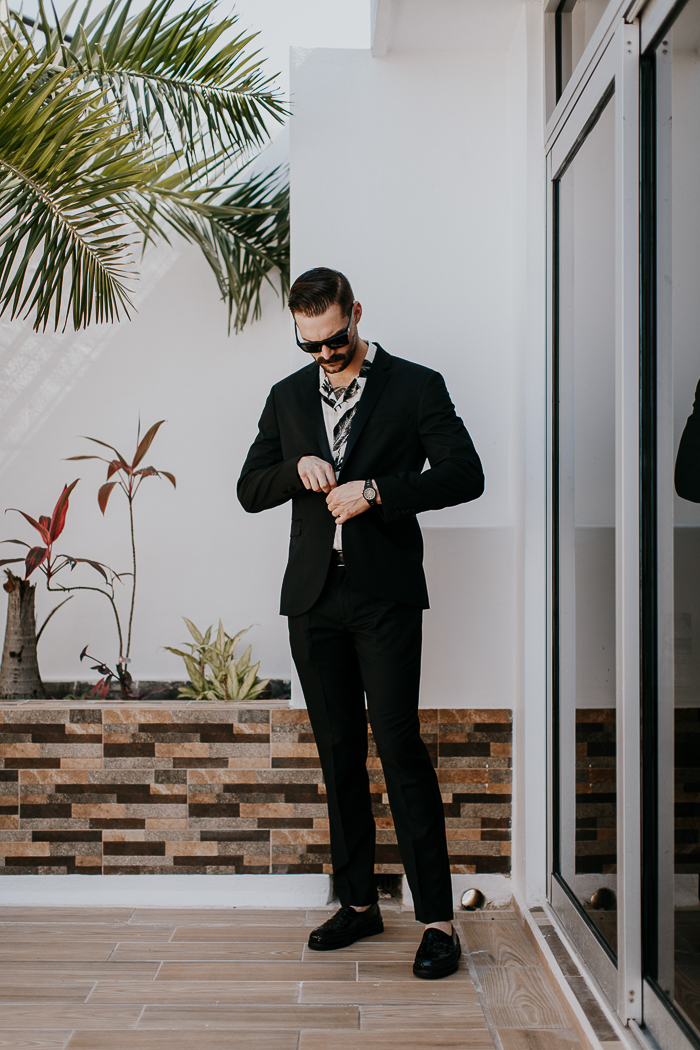 The groom was wearing a black suit with a tropical print shirt and black moccasins