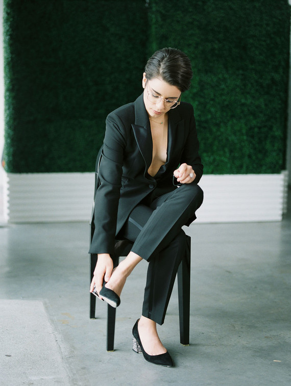 The second bride was wearing a stylish black pantsuit with no top, an emerald necklace and glasses