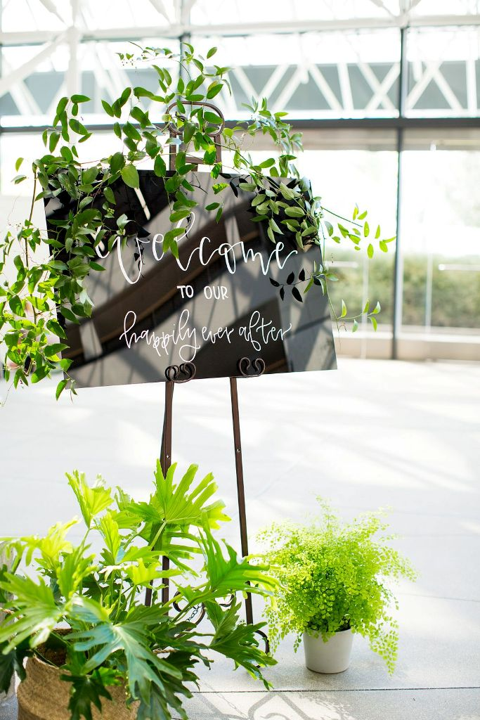 The wedding signage was modern, decorated with various kinds of greenery