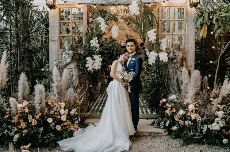 The wedding took place at a greenhouse cafe and inside it, the entrance was decorated with greenery, white orchids, pampas grass and more blush blooms around