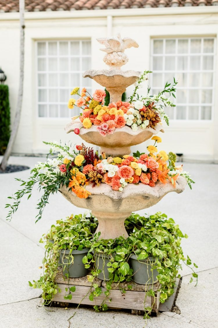 A vintage non-working fountain was filled with bright blooms and greenery and looked gorgeous