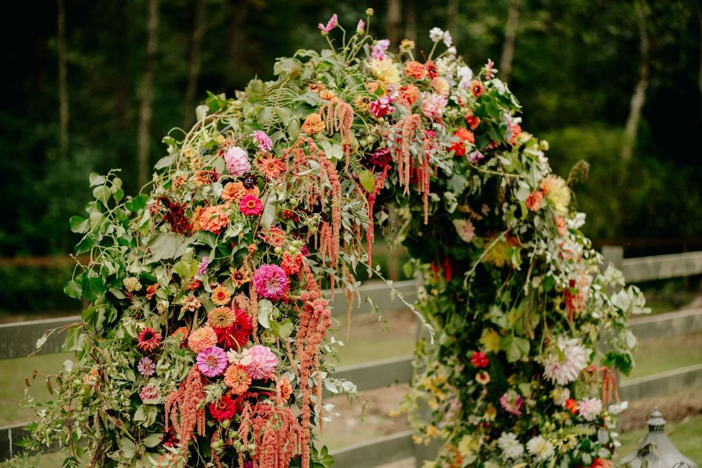 The fantastic wedding arch was done with bright blooms and greenery that were grown by the groom's family