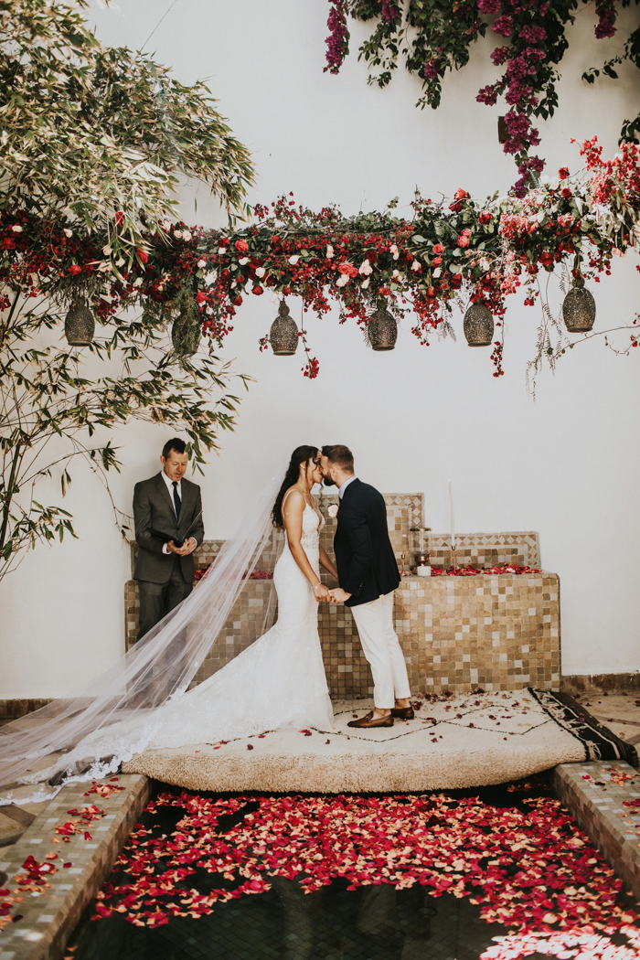 The wedding ceremony space was done with red and blush blooms and lots of greenery and petals