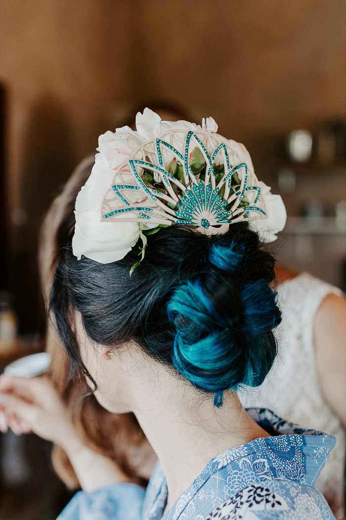 The wedding hair was a twisted updo with a whimsy peacock headpiece and white roses