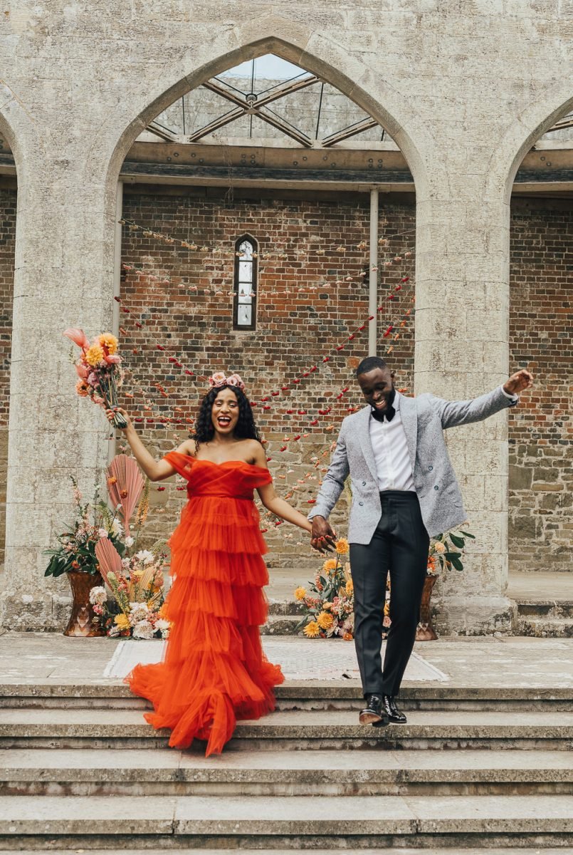 The bride was showing off an amazing off the shoulder fiery red ruffle wedding dress and a bold bouquet